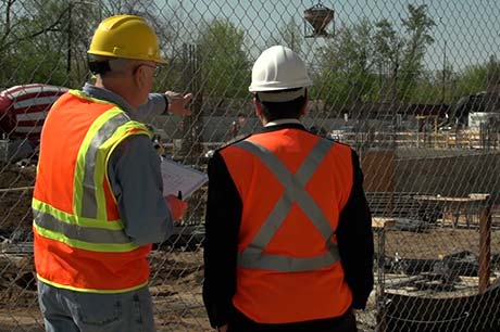 Set on a construction jobsite, two men wearing personal protective equipment, including hardhats and high-visibility safety vests, stand with their backs to the camera observing the jobsite.